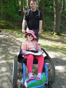 Annabelle in wheelchair in the forest. A man pushing the wheel chair. Both are smiling.