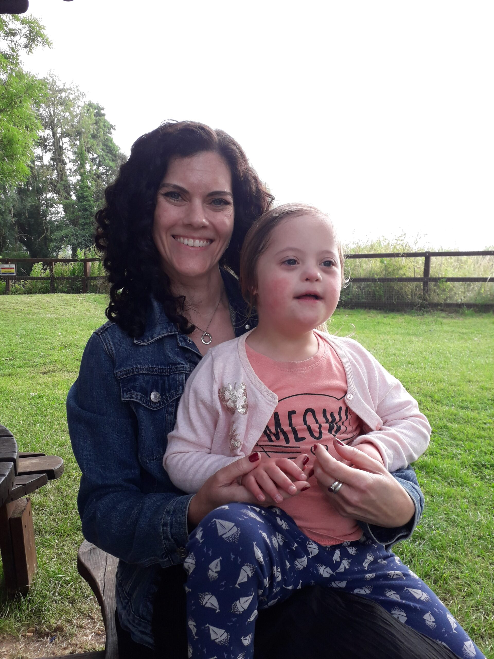 A mum with her daughter sat on her lap outside, both smiling.